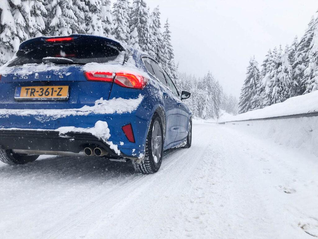 Auto in de sneeuw met vignet Oostenrijk 2021