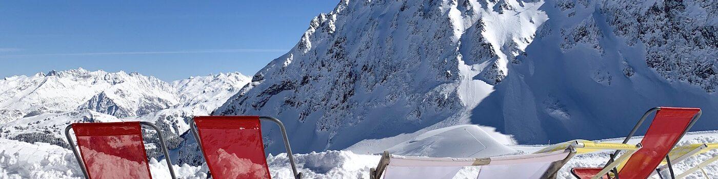 Ligstoeltjes op een rijtje in een skigebied in de zon