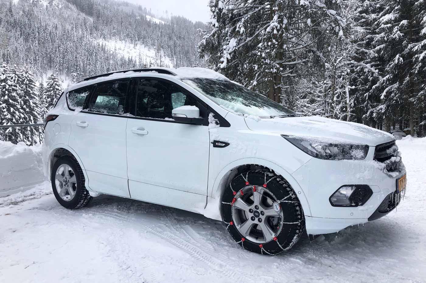 Auto met sneeuwkettingen op de weg in de sneeuw