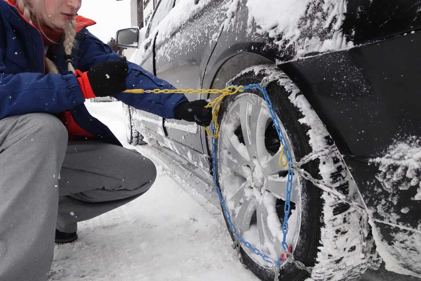 Sneeuwkettingen omleggen om de autobanden op wintersport