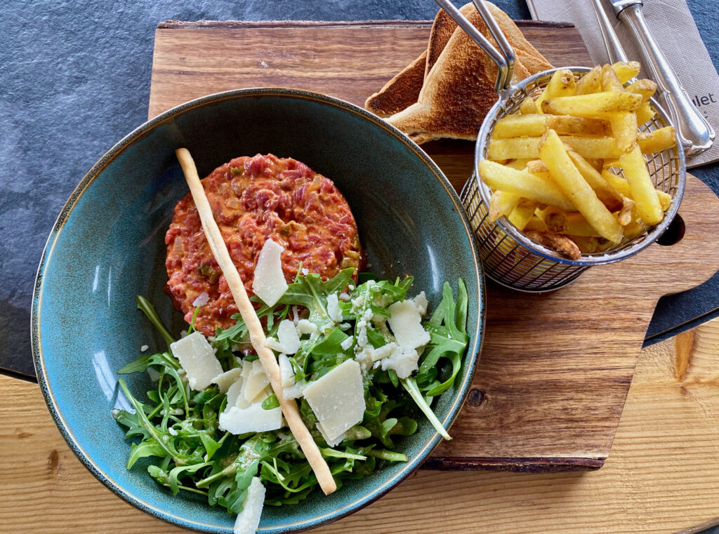 Bord met Tartaar, salade en frites bij Croiz-de-Culet
